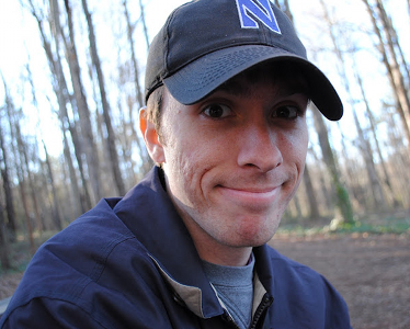 Brian DeConinck wearing a hat and jacket sitting in the woods.