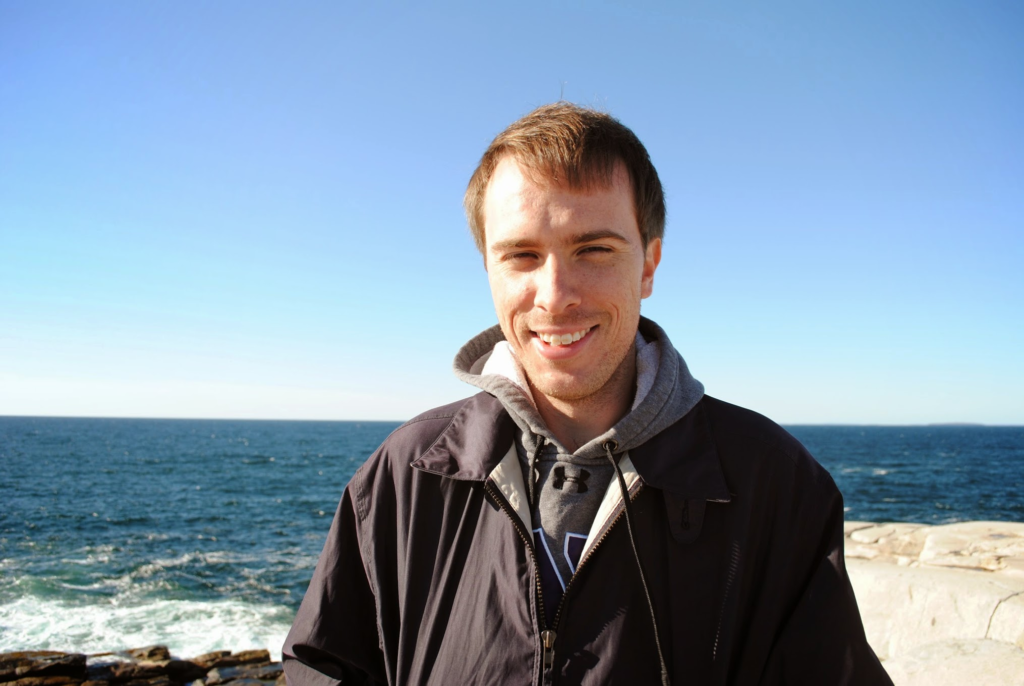 Brian DeConinck, standing in front of the ocean on a clear day.